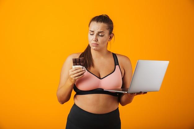 Portret młodej kobiety rozczarowanej nadwagą noszenia odzieży sportowej stojącej na białym tle nad żółtą ścianą, przy użyciu komputera przenośnego, trzymając tabliczkę czekolady