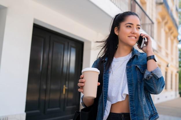 Portret młodej kobiety rozmawia przez telefon i trzymając filiżankę kawy, stojąc na zewnątrz na ulicy. koncepcja miejska i komunikacyjna.