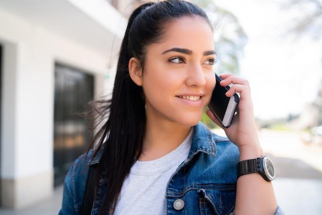Portret młodej kobiety rozmawia przez telefon, stojąc na zewnątrz na ulicy. koncepcja miejska i komunikacyjna.