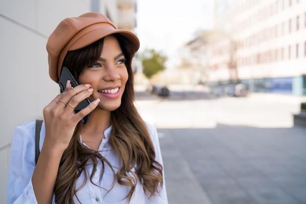 Portret młodej kobiety rozmawia przez telefon stojąc na zewnątrz na ulicy. koncepcja urbanistyczna i komunikacyjna.
