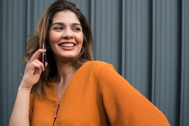 Portret młodej kobiety rozmawia przez telefon, stojąc na zewnątrz na ulicy