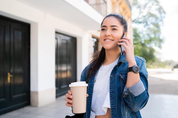 Portret młodej kobiety rozmawiającej przez telefon i trzymającej filiżankę kawy, stojąc na zewnątrz na ulicy