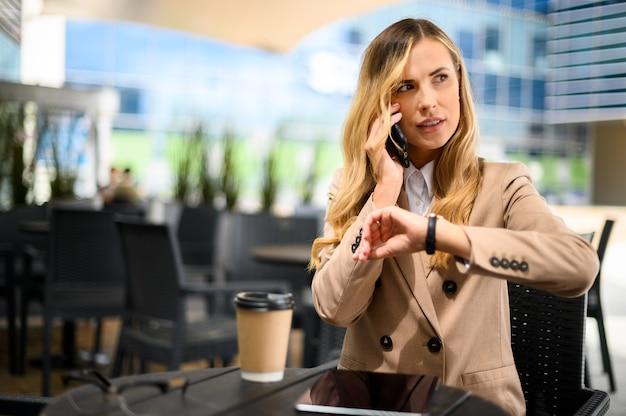 Portret młodej kobiety rozmawiającej przez telefon podczas przerwy i sprawdzania czasu na zegarku