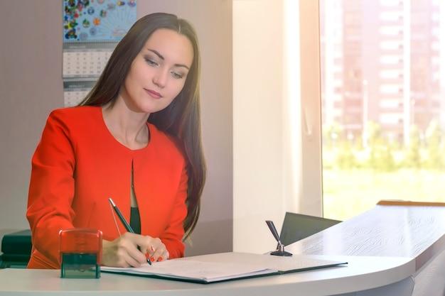 Portret młodej kobiety sekretarz podpisuje dokumenty