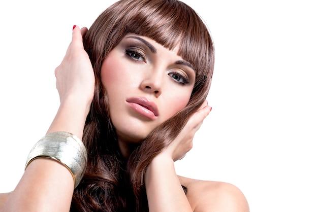 Portret młodej kobiety sexy z długimi brązowymi włosami. śliczna modelka ze stylową biżuterią w srebrnym kolorze.