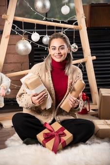 Portret młodej kobiety siedzącej i pozującej z prezentami. zdjęcie wysokiej jakości