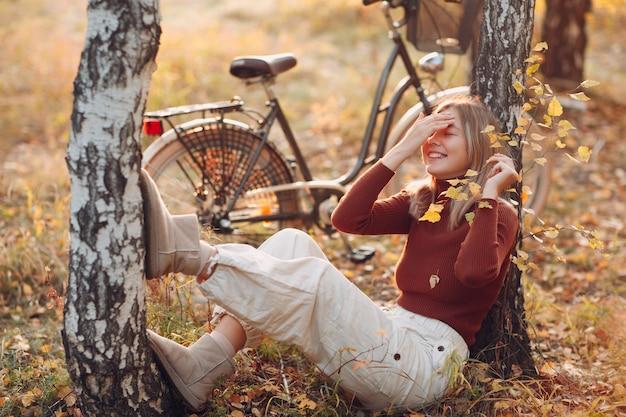 Portret młodej kobiety siedzącej obok roweru