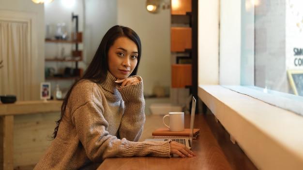 Portret młodej kobiety siedzącej przy drewnianym barze w kawiarni z papeterii i laptopa