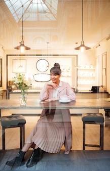 Portret młodej kobiety siedzącej przy nowoczesnej kawiarni
