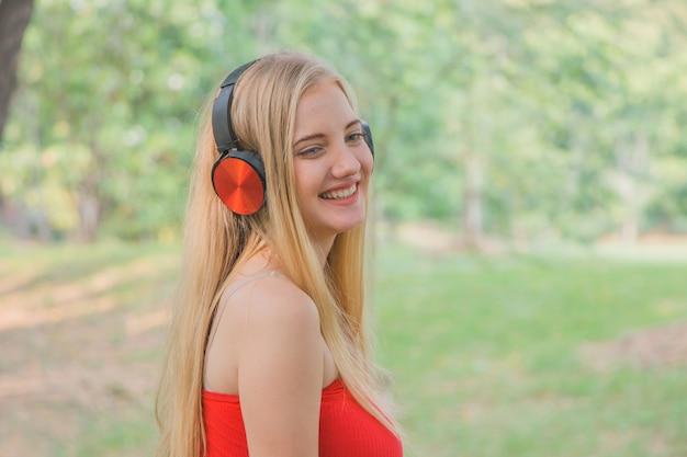 Portret młodej kobiety słuchania muzyki w słuchawkach i uśmiecha się w parku.