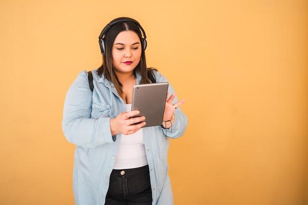 Portret młodej kobiety, słuchanie muzyki w słuchawkach i cyfrowy tablet na zewnątrz przed żółtą ścianą