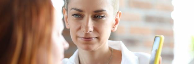 Portret młodej kobiety spędzać czas z najlepszym przyjacielem. piękna kobieta z krótkimi włosami pokazano coś na telefon komórkowy. komunikacja. relaks i wolny czas w domu koncepcja