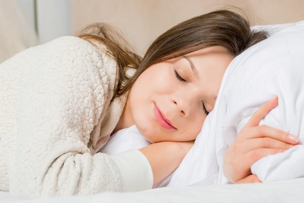Portret młodej kobiety śpi na łóżku w domu