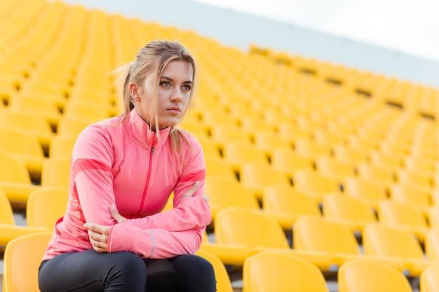 Portret młodej kobiety sportowe odpoczynku na stadionie
