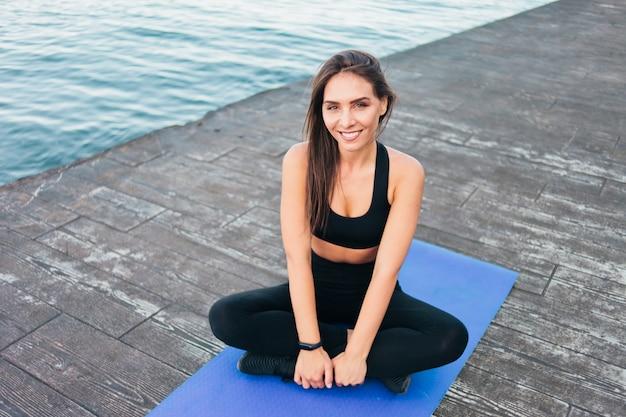 Portret młodej kobiety sportowe siedzi na macie na plaży.