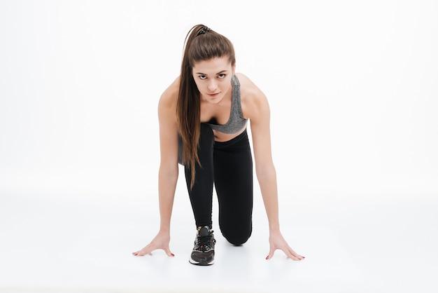 Portret młodej kobiety sportowej stojącej w pozycji startowej do biegania na białym tle