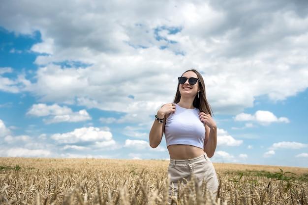 Portret młodej kobiety sportowy na polu pszenicy w lecie. styl życia