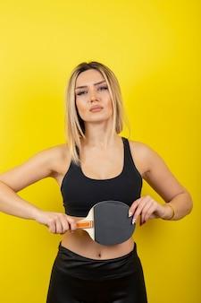 Portret młodej kobiety stojącej i trzymającej rakietę do tenisa stołowego na żółtej ścianie.