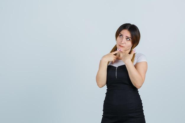 Portret młodej kobiety stojącej w myślącej pozie