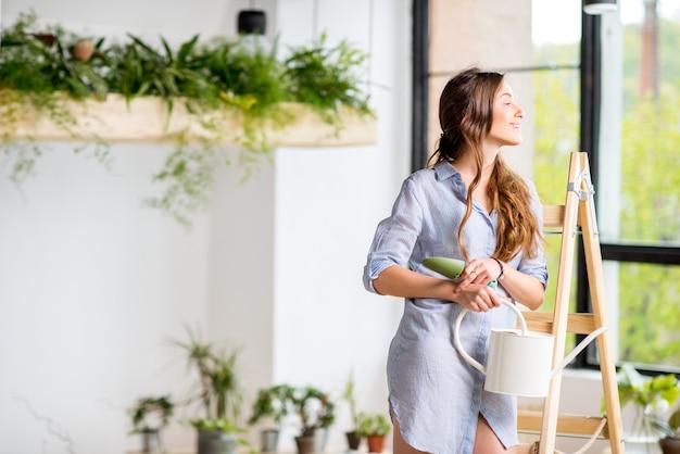 Portret młodej kobiety stojącej z konewką na drabinie w domu lub oranżerii z zielonymi roślinami
