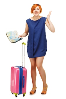 Portret młodej kobiety stojącej z różową walizką i mapą podróży, gestykulując na białym tle