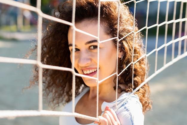 Portret młodej kobiety stwarzające obok boiska do siatkówki
