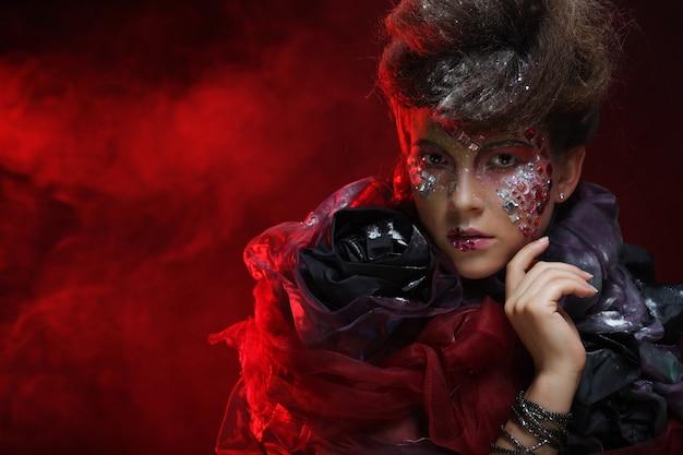 Portret młodej kobiety stylisn z twórczym obliczem na czerwonym tle.