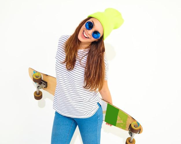 Portret młodej kobiety stylowe model w letnie ubrania w żółty czapka kapelusz pozowanie z biurkiem longboard. pojedynczo na białym