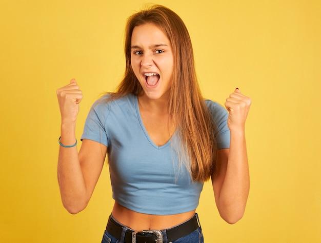 Portret młodej kobiety świętuje bycie zwycięzcą na żółtej ścianie