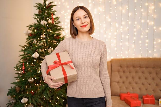 Portret młodej kobiety szczęśliwy czerwone usta patrząc na kamery trzymając zawinięte pudełko