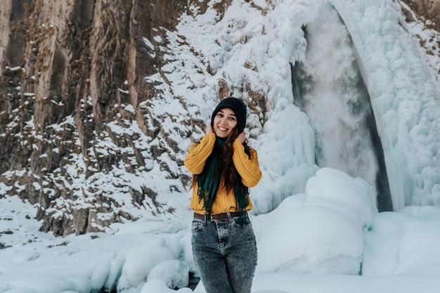 Portret młodej kobiety szczęśliwy przy wodospadzie. podróżuj do wodospadu zimą.