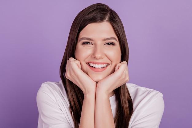 Portret młodej kobiety szczęśliwy uśmiech pięści podbródka na białym tle na fioletowym tle