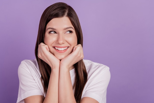 Portret młodej kobiety szczęśliwy uśmiech pięści podbródka wyglądają na pustą przestrzeń odizolowaną na fioletowym tle