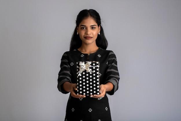 Portret młodej kobiety szczęśliwy uśmiechnięta dziewczyna trzyma pudełko na szarym tle.