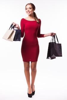 Portret młodej kobiety szczęśliwy uśmiechnięta z torby na zakupy, odizolowane na białej ścianie