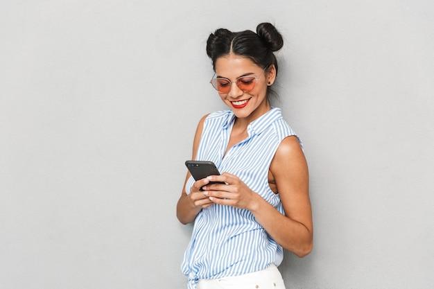 Portret młodej kobiety szczęśliwy w okularach przeciwsłonecznych na białym tle, przy użyciu telefonu komórkowego