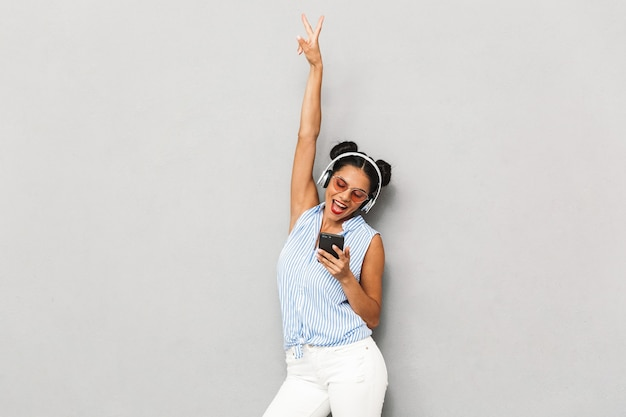 Portret młodej kobiety szczęśliwy w okularach przeciwsłonecznych na białym tle, trzymając telefon komórkowy, słuchanie muzyki w słuchawkach