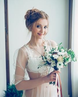 Portret młodej kobiety szczęśliwy z bukietem rano jej ślubu