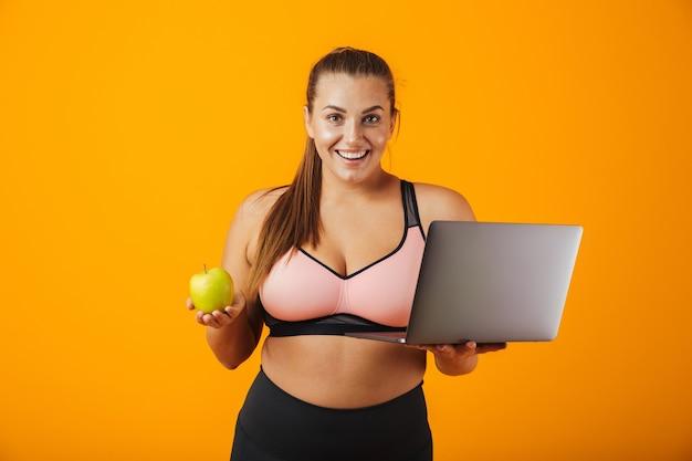 Portret młodej kobiety szczęśliwy z nadwagą noszenia odzieży sportowej stojącej odizolowane na żółtej ścianie, przy użyciu komputera przenośnego, trzymając zielone jabłko