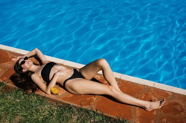 Portret młodej kobiety szczupła do opalania w pobliżu basenu hotelowego.