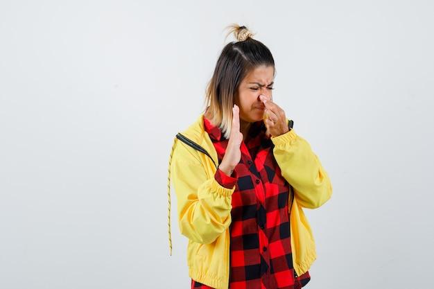 Portret młodej kobiety szczypiący nos z powodu nieprzyjemnego zapachu, pokazujący dłoń w kraciastej koszuli, kurtce i patrząc zniesmaczonym widokiem z przodu