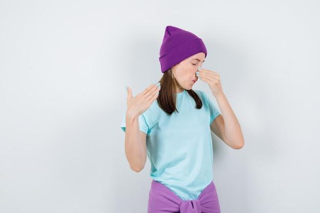 Portret młodej kobiety szczypie nos, wąchając coś okropnego w koszulce, czapce i patrząc zniesmaczonym widokiem z przodu