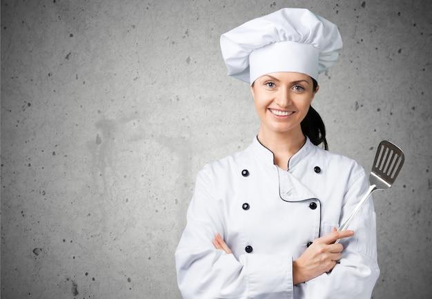 Portret młodej kobiety szefa kuchni na tle