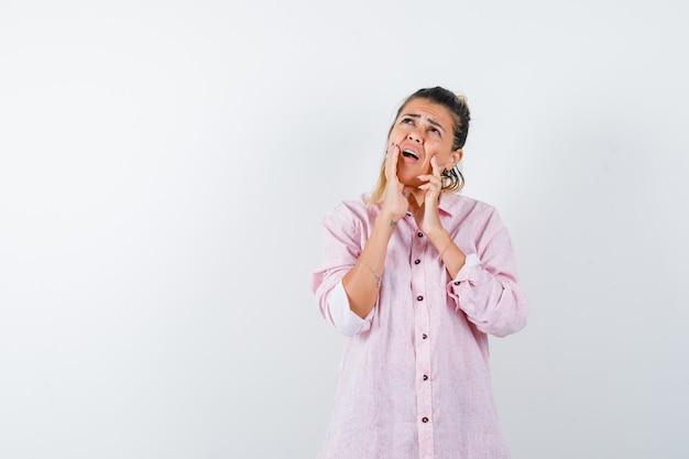 Portret młodej kobiety, trzymając ręce na policzkach w różowej koszuli i patrząc zmartwiony widok z przodu
