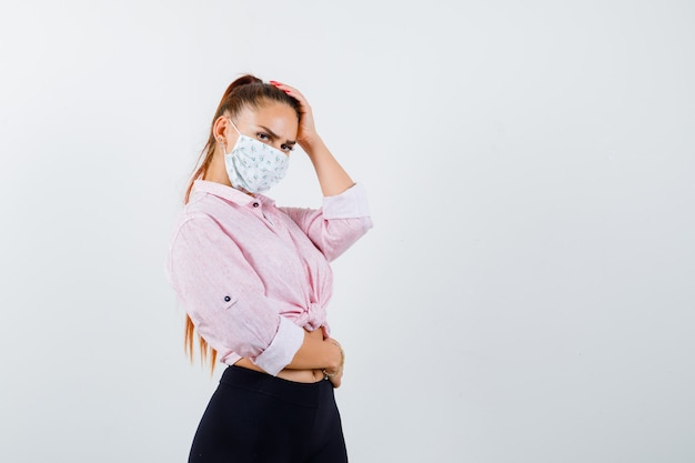 Portret młodej kobiety, trzymając rękę na głowie w koszuli, spodniach, masce medycznej i patrząc pewnie z przodu