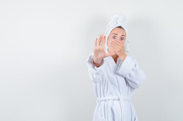Portret młodej kobiety, trzymając rękę na ustach, pokazując gest stop w biały szlafrok, ręcznik i patrząc przestraszony widok z przodu