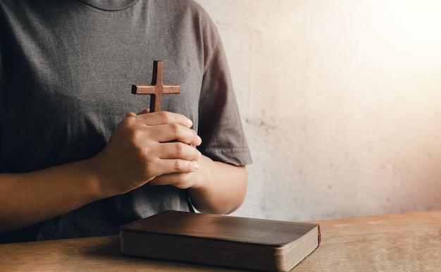 Portret Młodej Kobiety Trzymającej Biblię Mocno Przy Piersi. Gotowe Do Trzymania Krzyża Chrześcijaństwo Jest Gotowe Do Okazania Miłości Bogu. Premium Zdjęcia