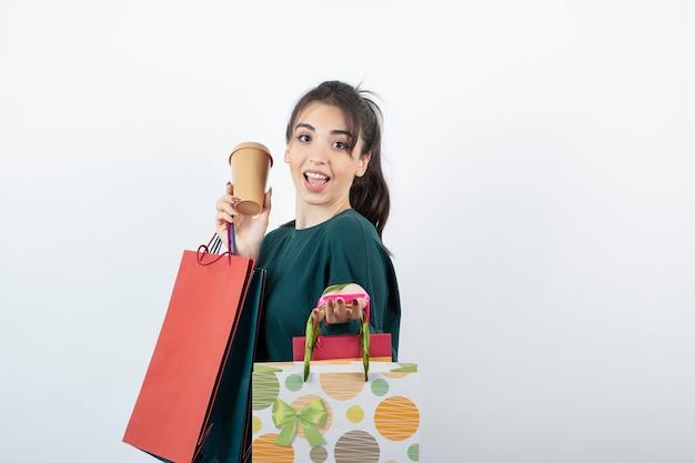 Portret młodej kobiety trzymającej filiżankę z kolorowymi torbami na zakupy.