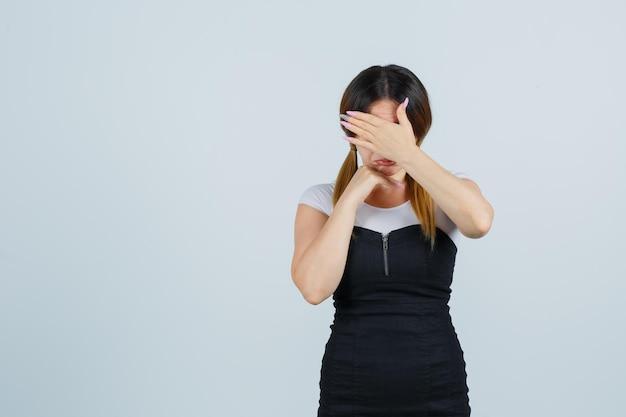 Portret młodej kobiety trzymającej jedną rękę nad oczami