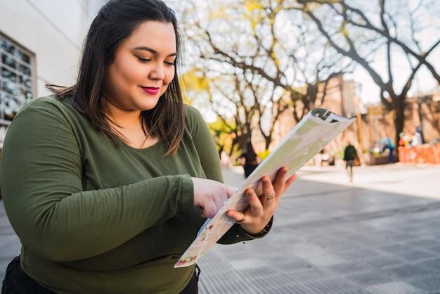 Portret młodej kobiety trzymającej mapę i szukającej wskazówek na zewnątrz na ulicy